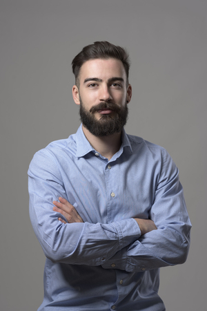 Confident successful young bearded entrepreneur man with crossed arms looking at camera against gray studio background.