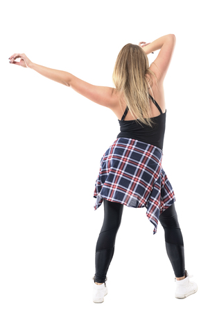 Back view of passionate woman dancing with one hand touching hair and one arm stretched. Full body length portrait isolated on white background. Banco de Imagens
