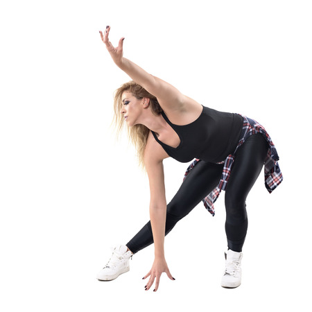 Sweaty woman aerobics instructor dancing jazz dance in bending posture. Full body length portrait isolated on white background.