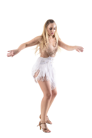 Backlit female professional dancer dancing salsa in fringed cream color dress costume. Full body length portrait isolated on white studio background.