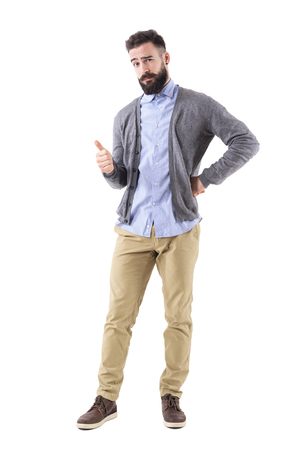 Stylish bearded smart casual guy wearing cardigan showing thumb up gesture and look at camera. Full body length portrait isolated on white background