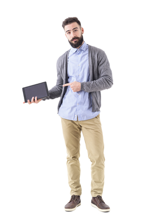Confident bearded stylish business man pointing at blank pad tablet computer screen. Full body length portrait isolated on white studio background. Stock Photo