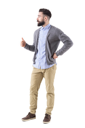 Confident bearded business man showing thumbs up looking away. Side view. Full body length portrait isolated on white studio background.