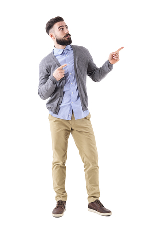 Uncertain confused bearded man pointing fingers up and looking above. Full body length portrait isolated on white studio background.