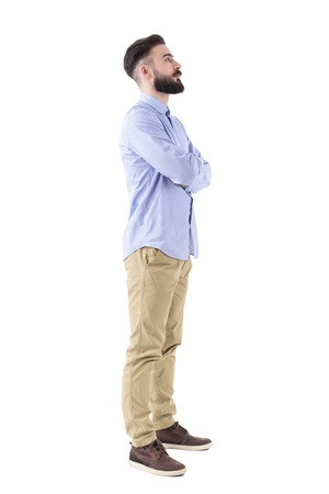 Profile view of bearded young adult business man with crossed arms looking up. Full body length portrait isolated on white studio background.