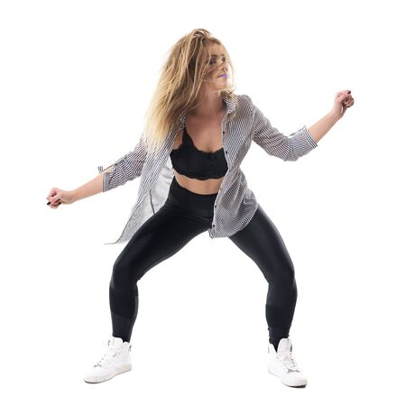 Front view of crouching aerobics jazz dance instructor with tousled hair and moving clothes. Full body length portrait isolated on white background. Stock Photo