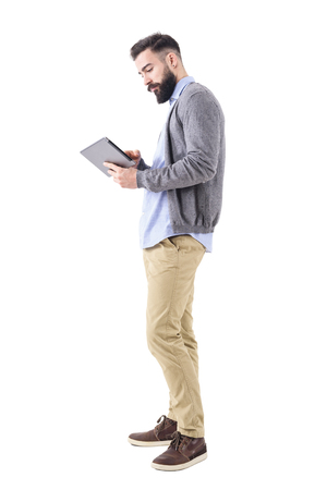 Professional young adult businessman using and looking at tablet computer. Side view. Full body length portrait isolated on white studio background.