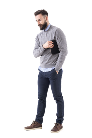 Serious thoughtful business man carry notebook under the arm and looking down. Full body length portrait isolated on white studio background.