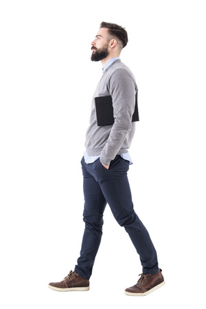 Confident serious businessman walking and carrying planner under arms. Side view. Full body length portrait isolated on white studio background.
