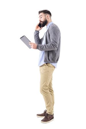 Stylowy młody dorosły biznesmen rozmawia przez telefon patrząc na komputer typu tablet pad. Portret długość całego ciała na białym tle na tle białego studia. Zdjęcie Seryjne