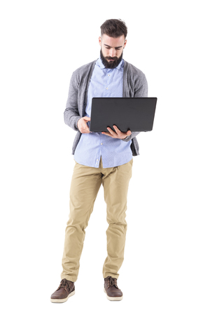 Front view of serious businessman holding and looking at laptop computer. Full body length portrait isolated on white studio background.