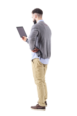 Back view of stylish modern businessman holding tablet with hand on hip. Full body length portrait isolated on white studio background.