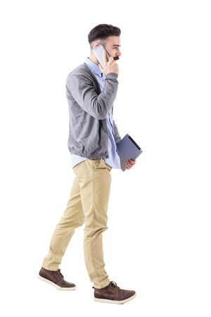 Confident young businessman with tablet on the phone, walk and look away. Full body length portrait isolated on white studio background. Stock Photo