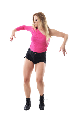 Attractive blonde woman dancing jazz dance in short, boots and pink shirt. Full body length portrait isolated on white studio background.