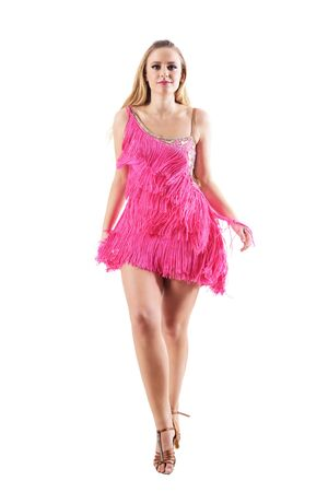 Front view of blonde woman in fringed dress walking and looking at camera. Full body length portrait isolated on white studio background.