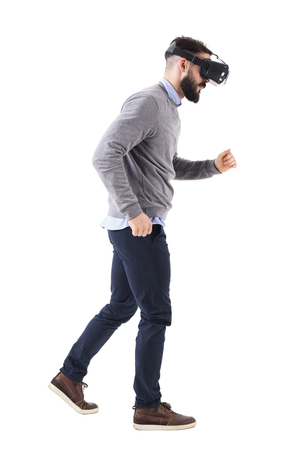 Side view of bearded man watching virtual reality glasses running and looking down. Full body isolated on white background. Stock Photo