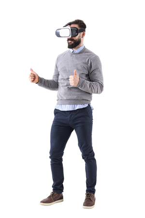 Smart casual business man wearing and watching vr glasses with thumbs up gesture. Full body isolated on white background.