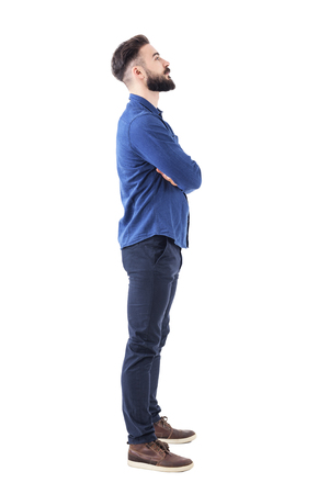 Smart casual bearded business man with crossed arms looking up above. Full body portrait isolated on white background. Stock Photo