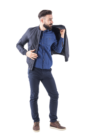 Bearded handsome man putting on bomber jacket and looking away. Full body length portrait isolated on white studio background. Фото со стока