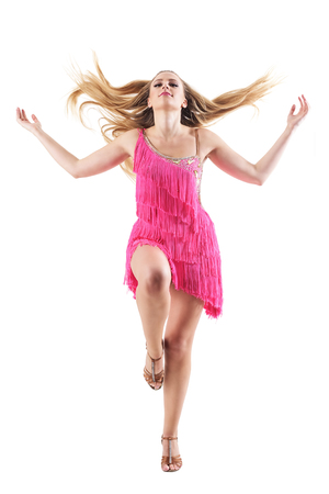 Professional female dancer tossing hair during dance performance in pink fringed dress. Full body isolated on white background.