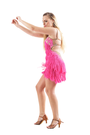 Ecstatic female dancer dancing with hands raised looking down wearing pink fringed costume. Full body isolated on white background. Stock Photo