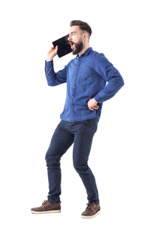 Funny bearded business man yelling on oversized large cell phone or tablet concept. Full body isolated on white background.