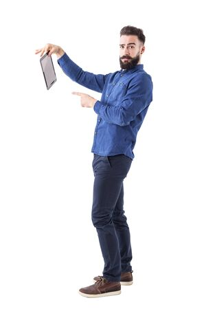 Offended young businessman holding and pointing finger at tablet computer looking at camera. Full body isolated on white background.