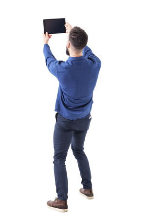 Rear back view of elegant handsome business man taking selfie photo with tablet. Full body isolated on white background.