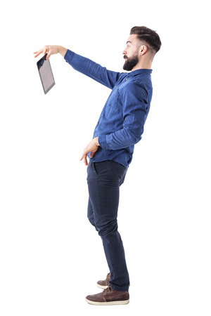 Shocked bearded businessman holding tablet with two fingers. Displeased concept. Full body isolated on white background.