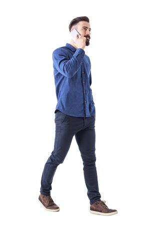 Successful stylish young male ceo walking and talking on the cell phone looking up. Full body isolated on white background. Stock Photo