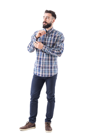 Confident serious macho bearded man buttoning sleeve button getting dressed looking away. Full body isolated on white background.