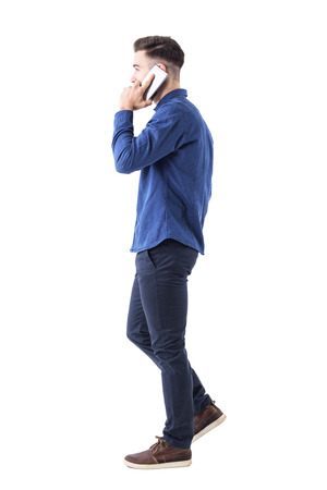 Profile of young successful business man on the phone walking and looking away. Full body isolated on white background.