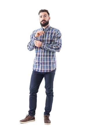 Young bearded man get dressed buttoning sleeve buttons and looking confidently at camera. Full body isolated on white background.