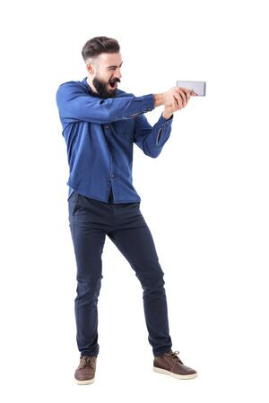 Playful business man holding mobile phone as pistol aiming as action movie hero. Full body isolated on white background.