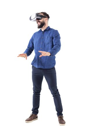 Excited young business man watching vr glasses laughing and gesturing with hands. Full body isolated on white background.