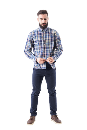 Relaxed cool bearded hipster buttoning plaid checkered shirt looking down. Full body isolated on white background.
