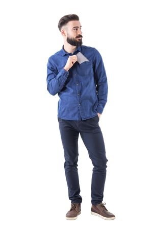 Handsome cool relaxed bearded guy put cellphone in shirt pocket looking away. Full body isolated on white background.
