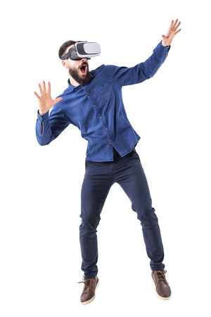 Scared shocked bearded adult man having virtual reality headset experience with open mouth. Full body isolated on white background. Imagens