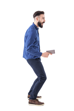 Childish playful expressive young adult business man holding cellphone as pistol and aiming away. Full body isolated on white background. Stock Photo