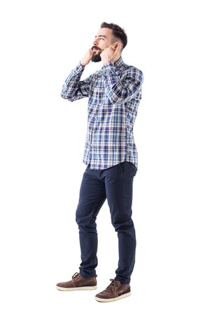 Young bearded hipster in checked shirt petting and stroking beard looking away. Full body isolated on white background.