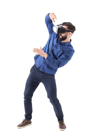 Young adult bearded man with vr glasses bending and shielding with hands playing video game. Full body isolated on white background.