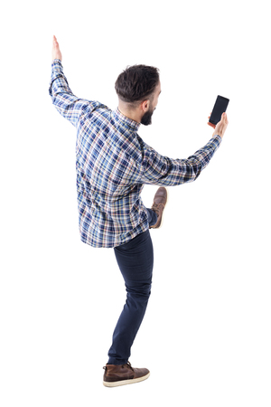 Excited young man holding mobile phone reading message on blank screen falling backwards. Rear view. Full body isolate on white background. 免版税图像