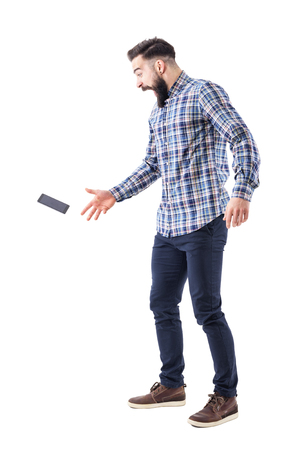 Screaming shocked young bearded man dropping mobile phone falling on the ground in mid air. Full body isolated on white background. 스톡 콘텐츠