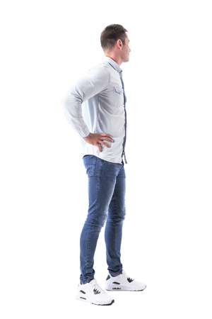 Young stylish business man with hands on hips looking away. Side view. Full body isolated on white background.
