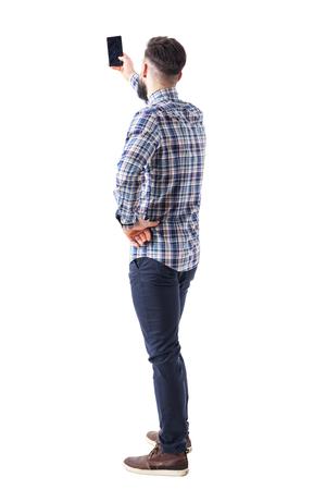 Vista posterior del hombre adulto tomando fotos o selfie con smartphone. Cuerpo completo aislado sobre fondo blanco.
