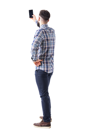Vue arrière d'un homme adulte prenant une photo ou un selfie avec un smartphone. Corps entier isolé sur fond blanc.