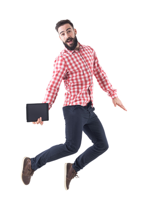 Successful excited young business man holding tablet jumping in mid air with open mouth. Full length isolated on white background. 免版税图像 - 104879522