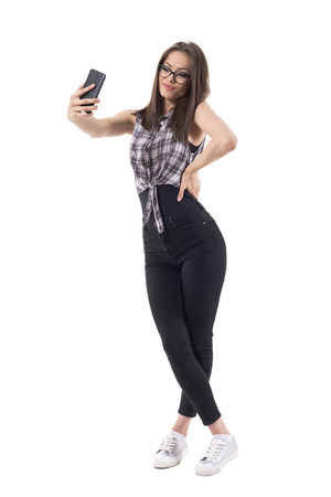 Cute young lovely stylish lady with glasses taking selfie photo looking at mobile phone. Full body isolated on white background.