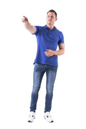 Relaxed casual man showing way directions pointing finger away and looking up. Full body isolated on white background.