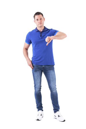 Unsure confused adult man in blue polo shirt showing thumbs down and looking up doubtfully. Full body isolated on white background. Banque d'images